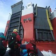Greenpeace volunteers in kayaks, speed boats and climbers on the jetty prevent the 23,498-tonne cargo ship Elbe Highway from docking at Sheerness in the Thames Estuary. The cargo ship is bringing Volkswagen diesel cars into the UK and the Greenpeace action is to prevent this from happening and to make VW ditch diesel. Two climbers board the ship and hang a banner on the roll-on roll-off part of the ship preventing any cars from being off-loaded.<br />