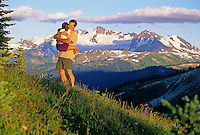 Dad and daughter hug during a break from a hike on Whistler Mountain on a summer evening. Whistler, BC Canada.