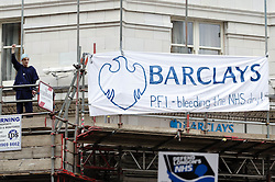 © Licensed to London News Pictures. 18/05/2013. London, UK. A protestor dressed as a doctor shouts alongside an anti-Barclays Bank banner draped over the entrance of one of the banks branches on the Strand in Central London, during a march by thousands of demonstrators held to protest against the Government's changes to the Health Service and planned closures to services across London.   Backed by Unite the Union, the Save Lewisham Hospital Campaign and MPs including Andy Slaughter and Steve Pound. Photo credit : Richard Isaac/LNP