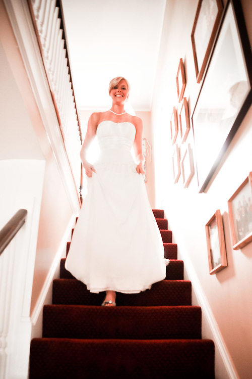 Jane comes down the stairs of her parents house in her wedding gown; Oak Park, IL