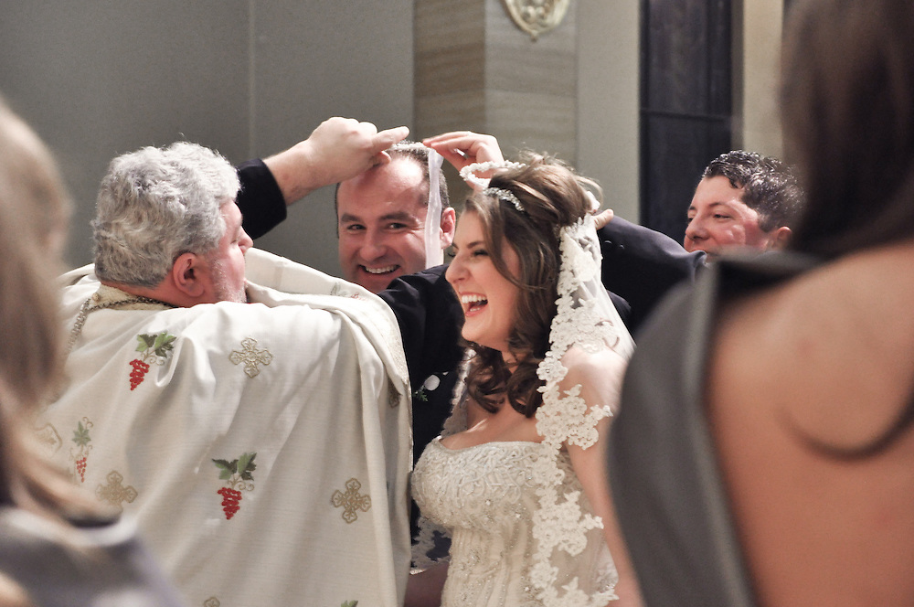 Mariana & Mark giggle during their crowning ceremony, St. Andrew's Greek Orthodox Church, Chicago