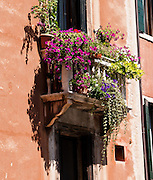 "Flower boxes bask in sun on a window balcony. Venice (Venezia) is the capital of Italy's Veneto region, named for the ancient Veneti people from the 10th century BC. The romantic ""City of Canals"" stretches across 117 small islands in the marshy Venetian Lagoon along the Adriatic Sea in northeast Italy, Europe. The Republic of Venice wielded major sea power during the Middle Ages, Crusades, and Renaissance. Riches from Venice's silk, grain, and spice trade in the 1200s to 1600s built elaborate architecture combining Gothic, Byzantine, and Arab styles. Venice and the Venetian Lagoons are honored on UNESCO's World Heritage List."