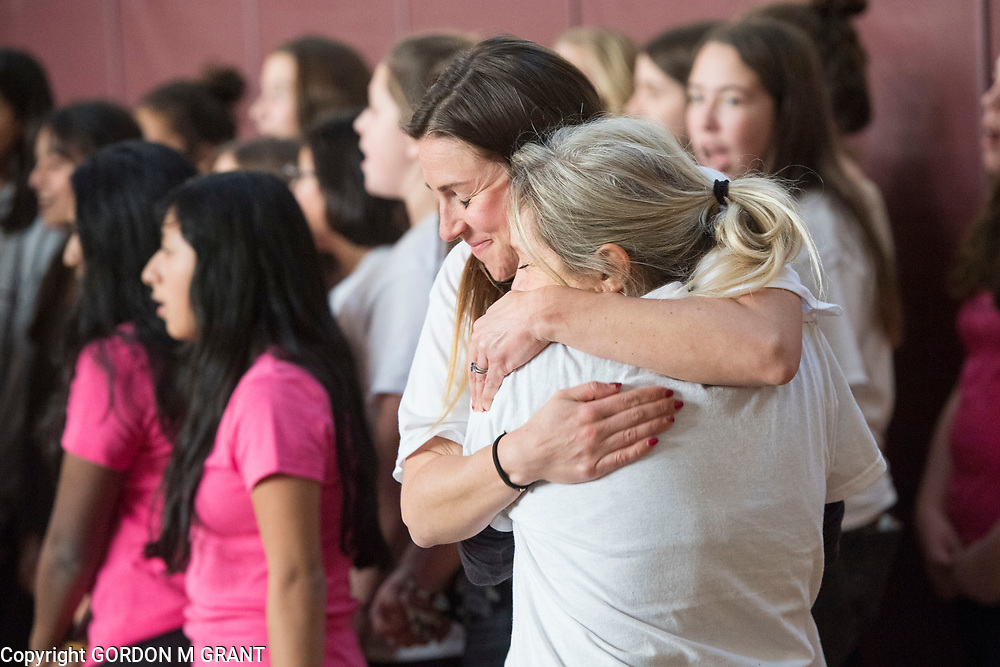 Cara Nelson, left, a 7th grade social studies teacher at the East Hampton Middle School, gets a hug from fellow teacher Lea Bryant, during a sendoff in her honor, at the school in East Hampton, Jan. 18, 2018. Nelson will leave next week to participate in a trip where she will run seven marathons in seven days on seven continents.