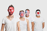 Portrait of serious Multi-ethnic group of male friends with various national flags painted on their faces standing against white background
