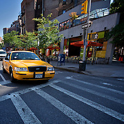 An iconic New York Yellow Taxi Cab waits at a crosswalk in busy Greenwich Village