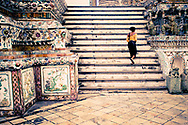 A young woman tourist walks up the stairs inside Wat Arun temple in Bangkok, Thailand.  Wat Arun is a buddhist temple (wat) and popular tourist attraction in Bangkok.