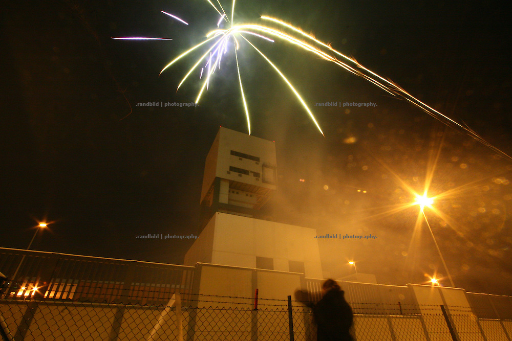 Anti nuclear activists protest while a sylvester party (2009-2010) against the future plans to implement a final dump of nuclear waste in Gorleben. The protesters welcomed the new year by fireing fireworks towards the sites tower. Police just observed the scenery.