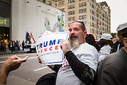 A male supporter of Donald J. Trump holding a Trump/Pence sign at a gathering on New York's Fifth Avenue in front of Trump Tower the Saturday before the November 2017 election