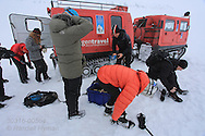 Tourists in April arrive by snowcat to explore ice cave formed inside glacier by annual meltwaters outside Longyearbyen on Spitsbergen island, Svalbard, Norway.