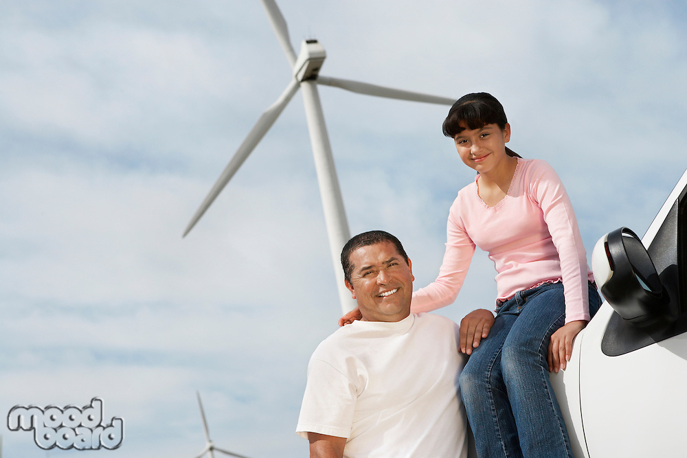 Father and daughter (7-9) at wind farm, portrait