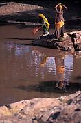 Women collecting water in brass jars, Oasis of Lourdhia, Rajasthan