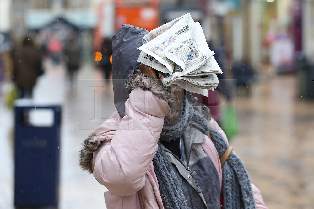 © Licensed to London News Pictures. 08/02/2015. Huddersfield, UK. A woman uses a newspaper to shield herself from the driving wind and rain in Huddersfield, West Yorkshire, as the town is battered by Storm Imogen. The UK is set to see more bad weather with high winds and flood warnings in place causing chaos and disruption to travel. Photo credit : Ian Hinchliffe/LNP