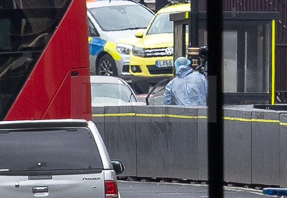 © Licensed to London News Pictures. 14/08/2018. London, UK. A police forensics photographer works near the silver car that crashed into barriers outside Parliament. A number of pedestrians are injured. The driver was arrested.  Photo credit: Peter Macdiarmid/LNP