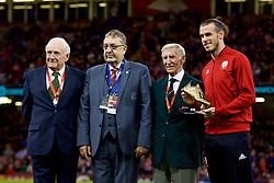 CARDIFF, WALES - Thursday, October 11, 2018: Wales' Gareth Bale (R) is presented with a golden boot for becoming the men's record goal-scorer by (L-R) Terry Medwin, FAW President Kieran O'Connor and Cliff Jones during the International Friendly match between Wales and Spain at the Principality Stadium. (Pic by Lewis Mitchell/Propaganda)