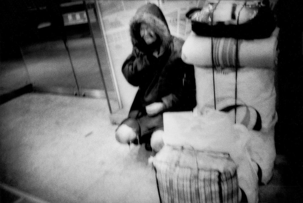 Homeless on streets / Elderly homeless man huddles for warmth on a winter night in Shinjuku Station.  In a few hours, he will be forced out into the cold night.  Tokyo, Japan.