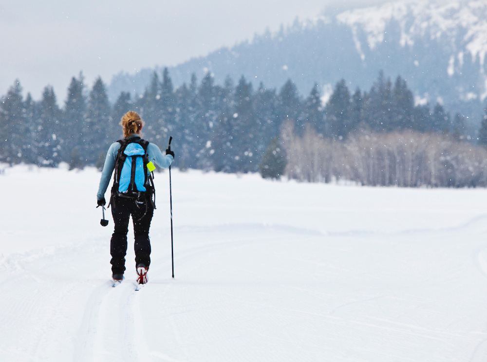 A woman skiing on the public groomed cross country ski trails in Mazama, Washington, USA. Methow Valley.