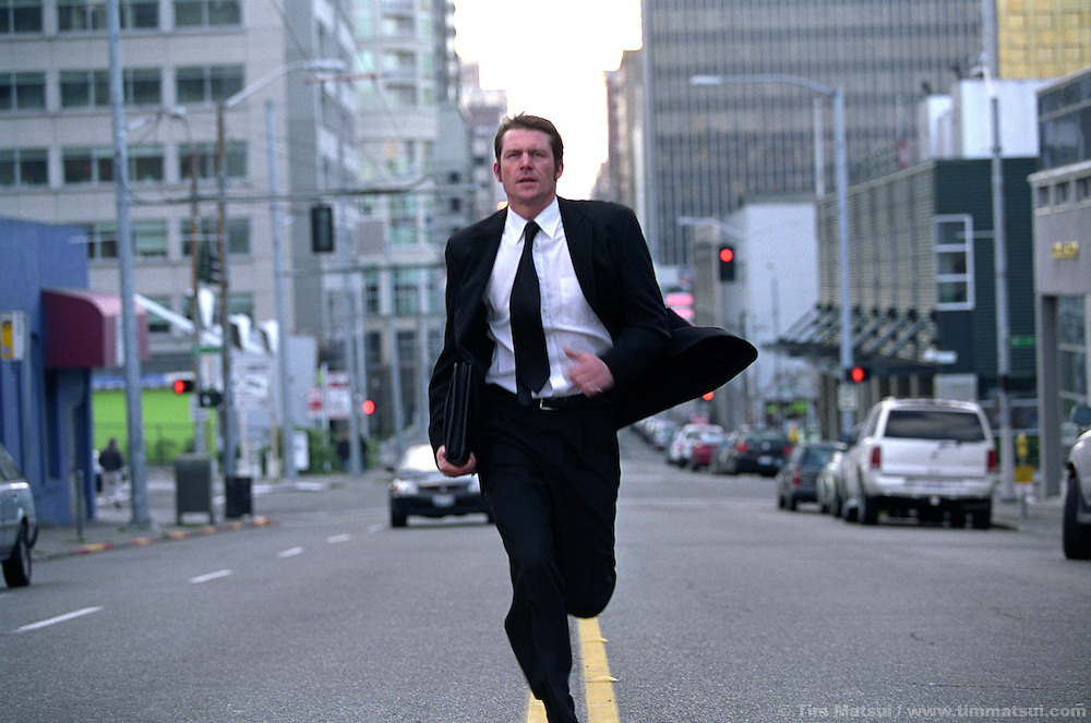 A caucasian man in a business suit runs down the street.