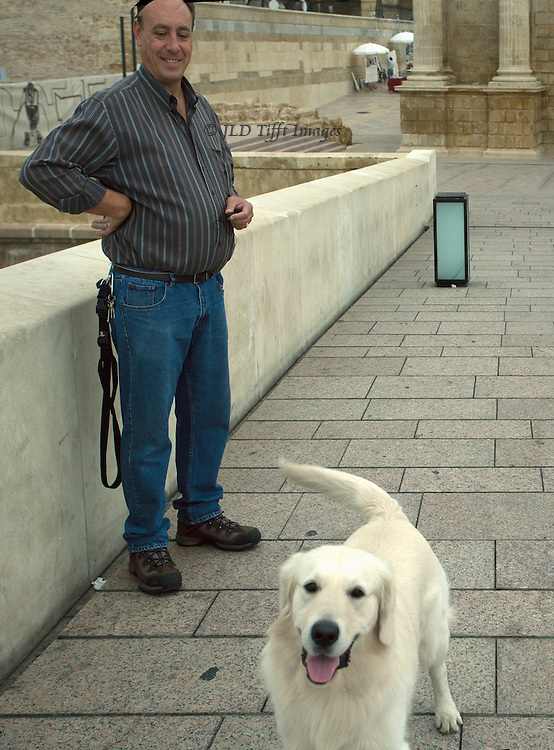 Beautiful white retriever poses willingly and obediently for the camera as his master looks on with approval.  On the Roman bridge into Cordoba, Spain.