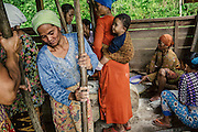 Women dehusking rice by hand. This activity is usually done in groups with long wooden sticks that act as pestles. The same sticks are also used to create  percussive music that help the women time their pounding to a rhythm.