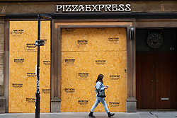 Glasgow, Scotland, UK. 17 July, 2020.  Images from Glasgow city centre as covid-19 restrictions are relaxed and  the public are out and about shopping and at work. Pictured; woman walks past closed and boasted up Pizza Express restaurant. Iain Masterton/Alamy Live News