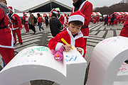 "Participants write Christmas messages on large letters spelling ""Santa"" before taking part in the Tokyo Great Santa Run in Komazawa-daigaku Olympic Park, Tokyo, Japan. Sunday December 22nd 2019, The great Santa Run was first run in Tokyo in 2018. This years run saw over 3,000 people in Santa costumes run and walk a 4.3 kilometre course to raise money for medical charities in japan and water projects for the Maasai in Kenya."