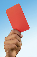 Soccer referee holding up red card close-up on hand