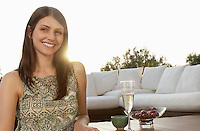 Young woman drinking champagne and eating fruit portrait