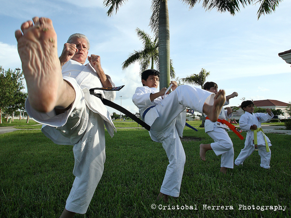 Karate coach Vicente Gonzalez, left, during his training session, with his students, at Sunset Lake Community Center on Monday July 6, 2009. Staff photo/Cristobal Herrera..