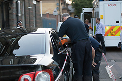© Licensed to London News Pictures. 25/07/2017. LONDON, UK.  Police forensic officers examine a car at the crime scene cordon on Burnham Street just off Roman Road this evening near Singh supermarket.  Two males in their late teens have been taken to hospital for treatment after an unknown liquid was thrown at them. Photo credit: Vickie Flores/LNP