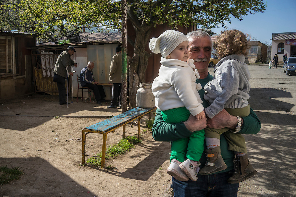 STEPANAKERT, NAGORNO-KARABAKH - APRIL 17: A man holds two small children after family members arrived from Yerevan on February 21, 2015 in Stepanakert, Nagorno-Karabakh. Since signing a ceasefire in a war with Azerbaijan in 1994, Nagorno-Karabakh has functioned as a de facto part of Armenia, with hostilities along the line of contact between Nagorno-Karabakh and Azerbaijan occasionally flaring up and causing casualties. (Photo by Brendan Hoffman/Getty Images) *** Local Caption ***