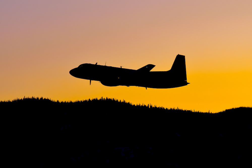 A Hawker-Siddeley HS 748 takes off in the glow of the pre-dawn sun
