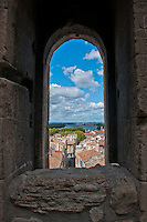 Looking out through an arched window over the ancient town of Arles from the Coliseum in France.