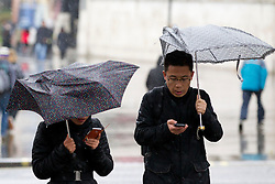 © Licensed to London News Pictures. 23/12/2013. London, UK. Two tourists check their mobile phones as they shelter beneath broken umbrellas at Trafalgar Square in London today (23/12/2013). Weather warnings were yesterday issued for the United Kingdom predicting severe wind and rain that may affect holiday travel. Photo credit: Matt Cetti-Roberts/LNP