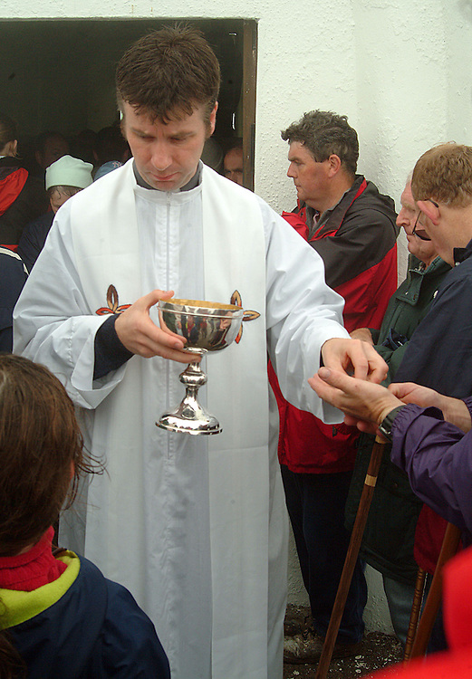 Fr. Micheal Mannion gives out communion during mass on Croagh Patrick on Garland Friday. Pic: Michael Mc Laughlin
