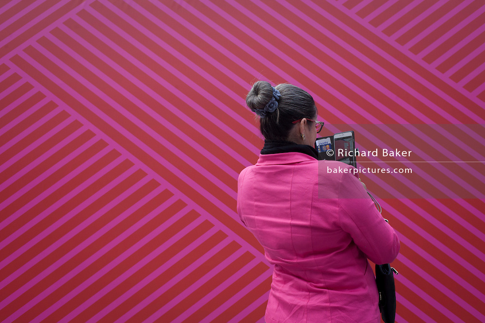 Woman and matching pink background of main venue for London Fashion Week at Somerset House.