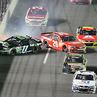 NASCAR Sprint Cup drivers Denny Hamlin (11) and Matt Kenseth (20)  wreck during the NASCAR Coke Zero 400 Sprint series auto race at the Daytona International Speedway on Saturday, July 6, 2013 in Daytona Beach, Florida.  (AP Photo/Alex Menendez)