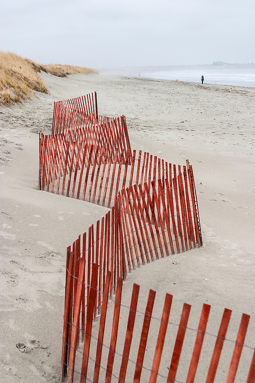 Red wind-break fencing zigzags along soft sand of Rhode Island beach