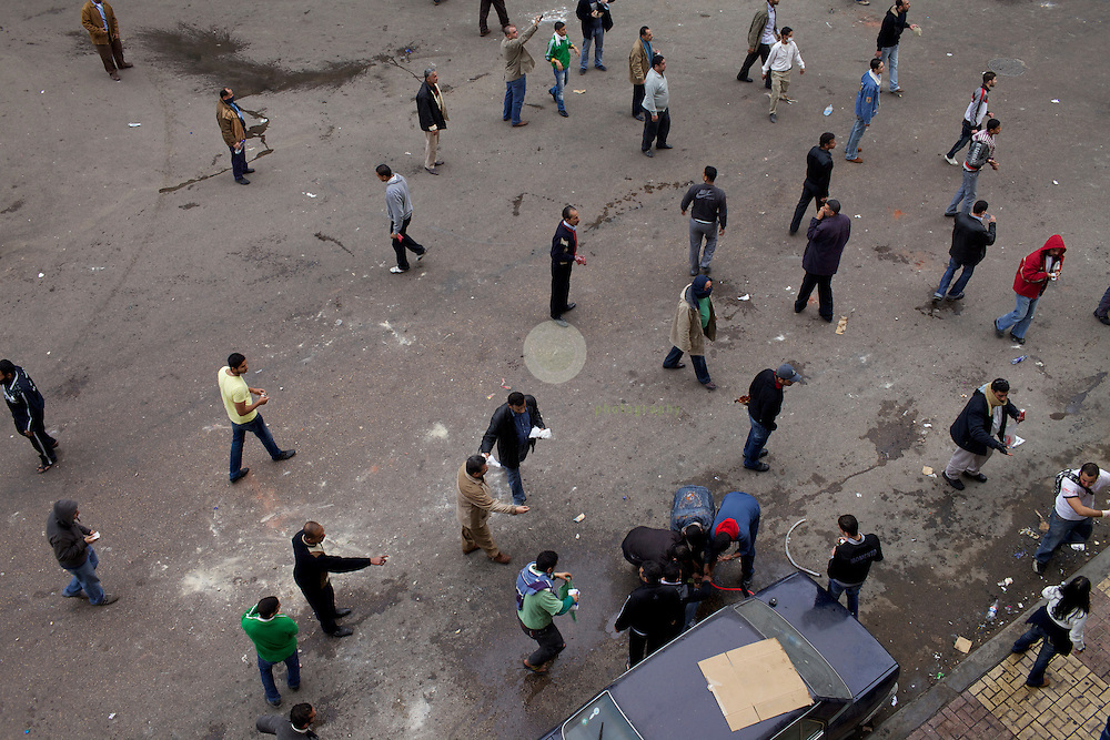 Anti-Mubarak protests in Alexandria. AFRICA, EGYPT, ALEXANDRIA,28.01.2011: after the Friday prayers protesters rally in thousands against the government. Huge numbers of security police forces are on the streets. Soon, the situation turns violent, with the police using tear gas and the demonstrators throwing stones and petrol bombs. These men are filling petrol from a car tank into a bottle.