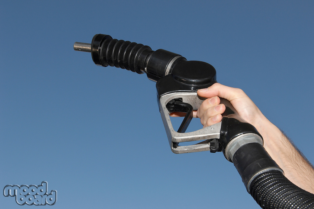 Person holding fuel pump against blue sky, close-up