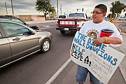 20 DECEMBER 2010 - PHOENIX, AZ: CARLOS OLIVAS collects donations to help pay for a liver transplant for Francisco Felix from passing motorists on 75th Ave in Phoenix, AZ. Most of the donations come in the form of dimes. Felix is a patient in AHCCCS, Arizona's Medicaid agency. He needs a liver transplant and is one of the patients Arizona Governor Jan Brewer (R) kicked off the transplant list when she eliminated funding for transplants from AHCCCS. The move saved the state of Arizona about $1.4 million. Olivas read the AHCCCS cuts and started collecting dimes to help pay for transplants the state of Arizona won't pay for. He said he does it because he wants to set an example for other young people and because he hopes someone would do the same thing for his father if he needed a liver transplant. Carlos said that so far he's collected about $2500.   PHOTO BY JACK KURTZ