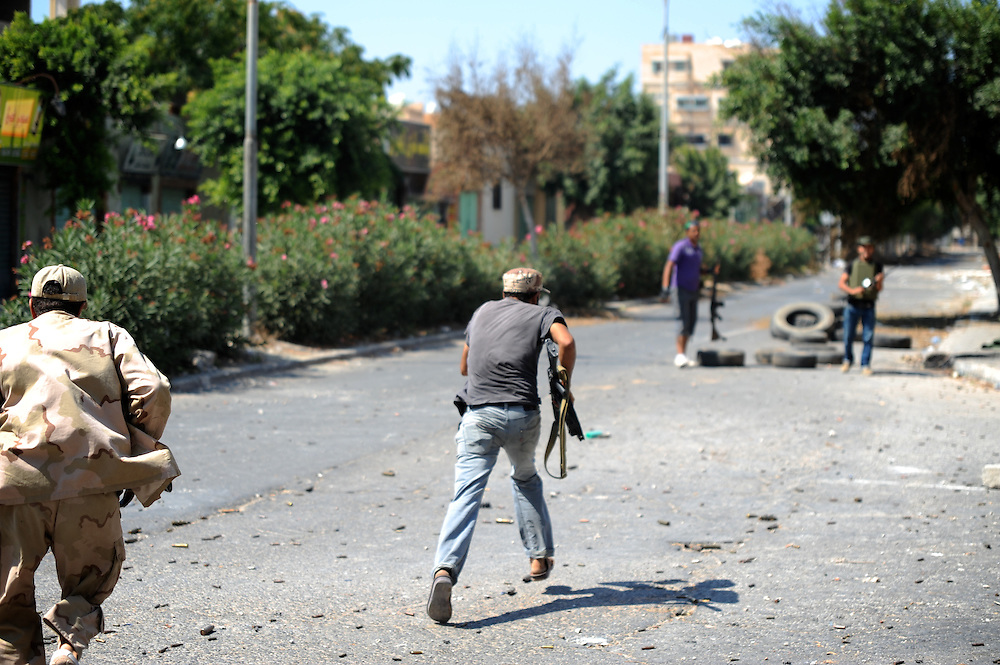Rebel fighters run to cover during intense fight against pro-Gaddafi troops in central Zawiyah.