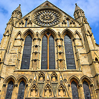 South Façade of York Minster in York, England<br /> The York Minster's southern façade was constructed in 1250 with an Early English Gothic design. The magnesian limestone glistens in the sunshine. The elegant centerpiece is the Rose Window, designed and created in 1515 by Robert Petty to celebrate the union of Lancaster and York. The wheel contains about 7,000 pieces of stained glass. Ravaged by fire in 1984, craftsmen toiled three years to reassemble 40,000 shards back into this beautiful work of religious art.