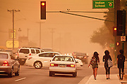"18 AUGUST 2011 - PHOENIX, AZ:    Teenagers walk down a street during a ""haboob"" in Phoenix Thursday. A haboob (Arabic for ""strong wind"") is a type of intense duststorm commonly observed in arid regions throughout the world. They have been observed in the Sahara desert, the Arabian Peninsula, throughout Kuwait, and most arid regions of Iraq. In the USA, they are frequently observed in the deserts of Arizona, including Yuma and Phoenix, as well as New Mexico and Texas. ""Haboob"" has been widely used to describe dust storms for more than a generation In Arizona but this year the very word ""haboob"" has become a political football because some conservatives have lobbied against use of the word, favoring English words, like ""dust storm.""      PHOTO BY JACK KURTZ"