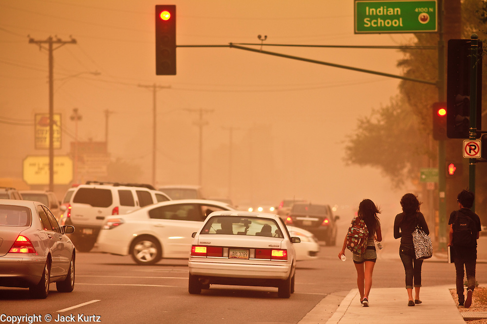 """18 AUGUST 2011 - PHOENIX, AZ:    Teenagers walk down a street during a """"haboob"""" in Phoenix Thursday. A haboob (Arabic for """"strong wind"""") is a type of intense duststorm commonly observed in arid regions throughout the world. They have been observed in the Sahara desert, the Arabian Peninsula, throughout Kuwait, and most arid regions of Iraq. In the USA, they are frequently observed in the deserts of Arizona, including Yuma and Phoenix, as well as New Mexico and Texas. """"Haboob"""" has been widely used to describe dust storms for more than a generation In Arizona but this year the very word """"haboob"""" has become a political football because some conservatives have lobbied against use of the word, favoring English words, like """"dust storm.""""      PHOTO BY JACK KURTZ"""