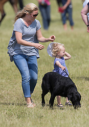 In the picture -Savannah in charge of family dog discards her sunhat but mother Autumn is quickly on the case.<br /> Peter Phillips the eldest grandchild of Queen Elizabeth II and Prince Philip, Duke of Edinburgh and his wife Autumn Phillips enjoyed a family day out with their children Savannah and Isla at the Barbury International Horse trials, Marlborough, Wilts.  They enjoyed the sunshine whilst watching  Zara Phillips compete in the event.<br /> Marlborough, Wilts, United Kingdom, July 06, 2013. Photo by: i-Images