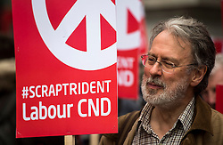 © Licensed to London News Pictures. 26/02/2016. London, UK. A man carrying an anti trident Labour CND banner as Thousands of people take part in a CND (Campaign for Nuclear Disarmament) rally in central London on February 27, 2016. Expected to attend the event are Labour leader Jeremy Corbyn,  leader of the SNP Nicola Sturgeon and Plaid Cymru's Leanne Wood. Photo credit: Ben Cawthra/LNP