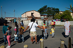 """Max Amansure gestures to organize social distance as a special chicken lunch is served by his Parkwood Community Upliftment (PCU) project, in Parkwood, Cape Town, South Africa, on Sunday, May 31, 2020. The youth organization, which normally feeds children as part of an after-school care program, has been feeding children and the elderly, and many other hungry people, in this poverty-stricken area in the Cape Flats since lockdown started more than two months ago. As the nation moves down to Level 3, on June 1st, CPU founder Amansure says the organization will continue to feed people. Often it's """"only"""" bread as the organization doesn't have any regular funding. However, as the area has been hard hit by COVID-19, Amansure says he wishes Parkwood could have remained on Level 5 Lockdown. PHOTO: EVA-LOTTA JANSSON"""