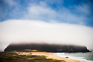 Fog rests along the remnant volcano core of Point Sur, with a view of the beach and blue Pacific Ocean waves at the California coast of Big Sur