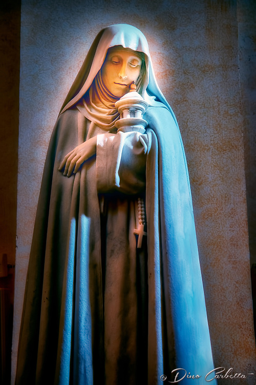 """""""Santa Chiara in the Cathedral of San Rufino Assisi""""...<br /> <br /> Clare was born in 1193 in Assisi of nobility, the oldest child. At 18, Clare escaped from her father's home one night, was met on the road by friars carrying torches, and in the poor little chapel called the Portiuncula received a rough woolen habit, exchanged her jeweled belt for a common rope, and sacrificed her long tresses to Francis' scissors. He placed her in a Benedictine convent, which her father and uncles immediately stormed in rage. Clare clung to the altar of the church, threw aside her veil to show her cropped hair, and remained adamant. Sixteen days later her sister Agnes joined her. Others came. They lived a simple life of great poverty, austerity, and complete seclusion from the world, according to a Rule which Francis gave them as a Second Order. At age 21, Francis obliged Clare under obedience to accept the office of abbess, one she exercised until her death. Contemporary accounts glow with admiration of Clare's life in the convent of San Damiano in Assisi. She served the sick and washed the feet of the begging nuns. She came from prayer, it was said, with her face so shining it dazzled those about her. She suffered a serious illness for the last 27 years of her life. Her influence was such that popes, cardinals, and bishops often came to consult her—Clare herself never left the walls of San Damiano. Francis always remained her great friend and inspiration. Clare was always obedient to his will and to the great ideal of gospel life which he was making real. A well-known story concerns her prayer and trust. Clare had the Blessed Sacrament placed on the walls of the convent when it faced attack by invading Saracens. """"Does it please you, O God, to deliver into the hands of these beasts the defenseless children I have nourished with your love? I beseech you, dear Lord, protect these whom I am now unable to protect."""" To her sisters, she said, """"Don't be afraid. Trust in Jesus."""" The Sara"""