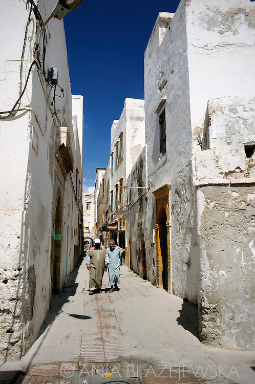 Morocco, Essaouira. Men walking the narrow streets of the medina in Essaouira.